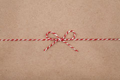 Jul stränger eller tvinnar bundet i en pilbåge på bakgrund för kraft papper royaltyfri fotografi