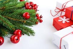 Jul tema för nytt år celebratory bakgrund Gåvaaskar, gröna prydliga filialer, dekorativa röda bär på vit Royaltyfria Foton