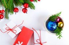 Jul tema för nytt år celebratory bakgrund Gåvaaskar, gröna prydliga filialer, dekorativa röda bär på vit Royaltyfria Bilder