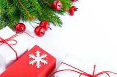 Jul tema för nytt år celebratory bakgrund Gåvaaskar, gröna prydliga filialer, dekorativa röda bär på vit Royaltyfri Bild
