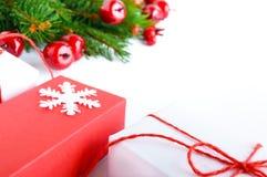 Jul tema för nytt år celebratory bakgrund Gåvaaskar, gröna prydliga filialer, dekorativa röda bär på vit Arkivbilder