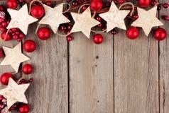 Jul tränga någon gränsen med lantliga wood stjärnaprydnader och struntsaker över åldrigt trä Royaltyfria Bilder