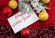 Jul undertecknar, julgranen i snön, guld- prydnader för jul Arkivfoto