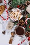 Jul varm choklad eller kakao med marshmallowen, kakor på vit bakgrund med julgarneringar Lekmanna- lägenhet royaltyfria bilder