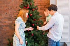 Jul x-mas, familj, folk, lyckabegrepp - lyckliga föräldrar med nätt behandla som ett barn pojken Arkivfoton