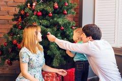 Jul x-mas, familj, folk, lyckabegrepp - lyckliga föräldrar med nätt behandla som ett barn pojken Arkivbilder