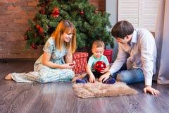 Jul x-mas, familj, folk, lyckabegrepp - lyckliga föräldrar med nätt behandla som ett barn pojken Arkivbild
