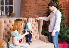 Jul x-mas, familj, folk, lyckabegrepp - lyckliga föräldrar med nätt behandla som ett barn pojken Arkivfoto