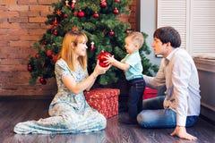 Jul x-mas, familj, folk, lyckabegrepp - lyckliga föräldrar som spelar med gulligt, behandla som ett barn pojken Arkivfoton