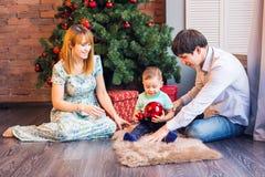 Jul x-mas, familj, folk, lyckabegrepp - lyckliga föräldrar som spelar med gulligt, behandla som ett barn pojken Arkivbilder