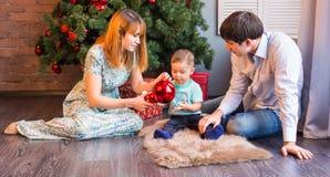 Jul x-mas, familj, folk, lyckabegrepp - lyckliga föräldrar som spelar med gulligt, behandla som ett barn pojken Arkivfoto