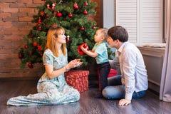 Jul x-mas, familj, folk, lyckabegrepp - lyckliga föräldrar som spelar med gulligt, behandla som ett barn pojken Royaltyfria Foton