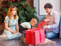 Jul x-mas, familj, folk, lyckabegrepp - lyckliga föräldrar som spelar med gulligt, behandla som ett barn pojken Royaltyfri Fotografi