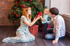 Jul x-mas, familj, folk, lyckabegrepp - lyckliga föräldrar som spelar med gulligt, behandla som ett barn pojken Arkivbild