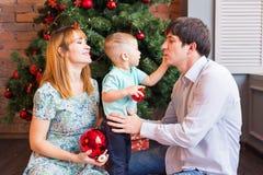 Jul x-mas, familj, folk, lyckabegrepp - lyckliga föräldrar som spelar med gulligt, behandla som ett barn pojken Royaltyfri Bild