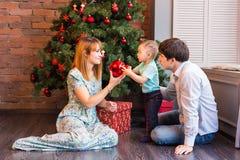 Jul x-mas, familj, folk, lyckabegrepp - lyckliga föräldrar som spelar med gulligt, behandla som ett barn pojken Royaltyfri Foto