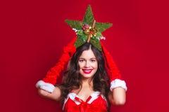 Jul x-mas, folk, lyckabegrepp - lycklig kvinna Stående av den härliga sexiga flickan som bär Santa Claus kläder med Kristus Arkivfoto