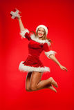Jul x-mas, vinter, begrepp - le kvinnan i santa hjälpredahatt med gåvaasken, lyckahopp för glädje över rött Arkivbild