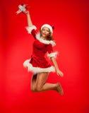 Jul x-mas, vinter, begrepp - le kvinnan i santa hjälpredahatt med gåvaasken, lyckahopp för glädje över rött Royaltyfri Foto
