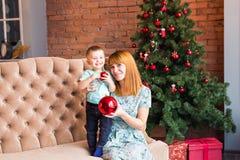 Jul x-mas, vinter, familj, folk, lyckabegrepp - den lyckliga modern med förtjusande behandla som ett barn pojken Arkivfoton