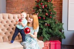 Jul x-mas, vinter, familj, folk, lyckabegrepp - den lyckliga modern med förtjusande behandla som ett barn pojken Royaltyfria Bilder
