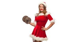 Jul x-mas, vinter, lyckabegrepp - bodybuilding Stark passformkvinna som övar med hantlar i den santa hjälpredan Arkivfoton