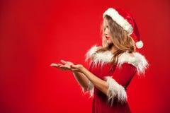 Jul x-mas, vinter, lyckabegrepp - le kvinnan i santa hjälpredahatt med gåvaasken som rymmer räcker framme av Arkivfoto