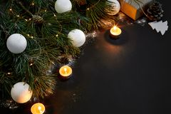 Jul Xmas-leksaker, brännande stearinljus och prydlig filial på bästa sikt för svart bakgrund Utrymme för text Arkivfoton