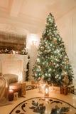 Julafton vid levande ljus klassiska lägenheter med en vit spis, dekorerat träd, ljus soffa, stora fönster Royaltyfri Bild