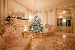 Julafton vid levande ljus klassiska lägenheter med en vit spis, dekorerat träd, ljus soffa, stora fönster Arkivbilder