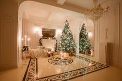 Julafton vid levande ljus klassiska lägenheter med en vit spis, dekorerat träd, ljus soffa, stora fönster Fotografering för Bildbyråer