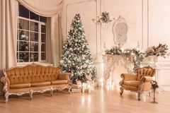 Julafton vid levande ljus klassiska lägenheter med en vit spis, ett dekorerat träd, soffa, stora fönster och fotografering för bildbyråer