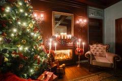 Julafton vid levande ljus klassiska lägenheter med en vit spis, ett dekorerat träd, soffa, stora fönster och Royaltyfria Bilder