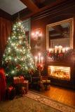 Julafton vid levande ljus klassiska lägenheter med en vit spis, ett dekorerat träd, soffa, stora fönster och Royaltyfri Bild
