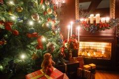 Julafton vid levande ljus klassiska lägenheter med en vit spis, ett dekorerat träd, soffa, stora fönster och Arkivfoto