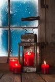 Julatmosfär: fyra röda bränningstearinljus i fönstret Arkivfoto