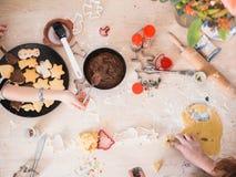Julbageri: Flickor som förbereder julkakor, bästa sikt med sifferent stekheta tillförsel royaltyfri foto