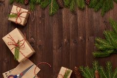Julbakgrund av gåvor, kraft papper, gran förgrena sig kottar tvinnar och sax royaltyfria foton
