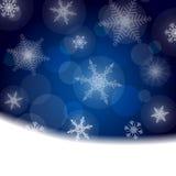 Julbakgrund - blått med vita snöflingor Arkivfoto