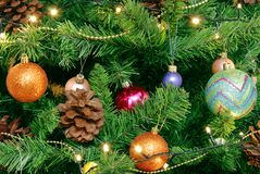 Julbakgrund för hälsningkort och platser Grön julgran med stora kottar Dekorerat med ljusa runda bollar, girlander arkivfoto