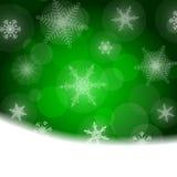 Julbakgrund - gräsplan med vita snöflingor Arkivbilder