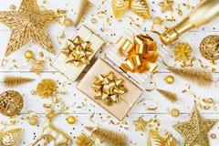 Julbakgrund med den guld- gåvan eller närvarande ask, champagne och feriegarneringar på den vita bästa sikten för tabell greeting arkivfoton