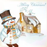 Julbakgrund med den hand drog snögubben och det lilla huset Royaltyfri Fotografi