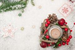 Julbakgrund med den konstgjorda snö, stearinljuset och julgranfilialer Top beskådar royaltyfri foto