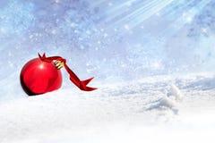 Julbakgrund med den röda baublen i snowen Arkivbilder