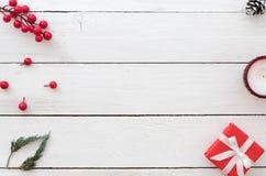Julbakgrund med den röda gåvaasken, järnekbäret, gransidor, sörjer kotten och undersöker på vit träbakgrund fotografering för bildbyråer