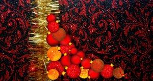 Julbakgrund med den röda och gula prydnaden på en svart blänker texturerad bakgrund arkivfoto