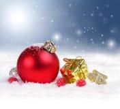 Julbakgrund med den röda prydnaden och snöflingor Royaltyfri Fotografi