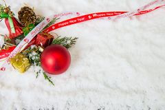 Julbakgrund med den röda struntsaken, snö och snöflingor Royaltyfri Foto