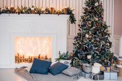 Julbakgrund med det upplysta granträdet och spis på huset royaltyfria bilder